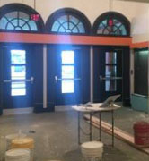 The theatre lobby, following a fresh coat of paint, would become a soft white color. Here, only primer is applied. Courtesy of Leeds Center for the Arts