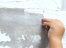 Thumbnail: Child's hand peeling paint off of a wall