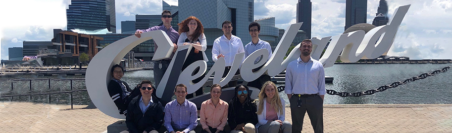 Research analysts at the Cleveland Fed pose by the Cleveland sign