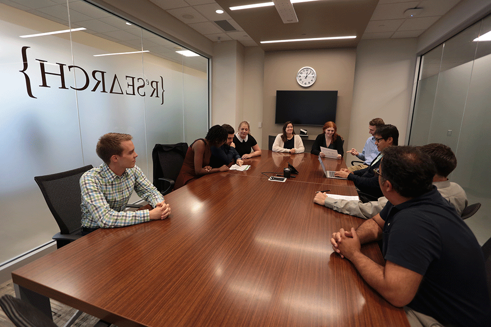 A photo of a meeting room with Cleveland Fed research analysts and economists