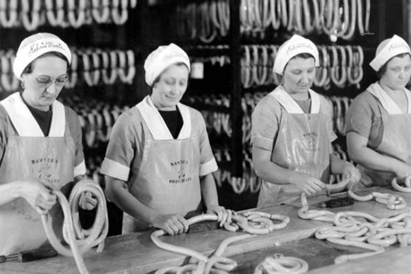Starting as a small butcher shop in 1882, the manufacturing plant in which these women are making hot dogs was established by Kahn's Meat Company in Cincinnati, Ohio. The plant was purchased by Consolidated Foods Corporation in 1966, and it remained open until the land was sold to Hamilton County in 2006.