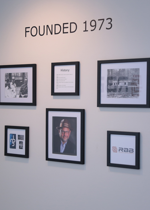 People visiting RBB, a manufacturer in Wooster, can see the company's founders, a brief history, and its logos on the front lobby wall.